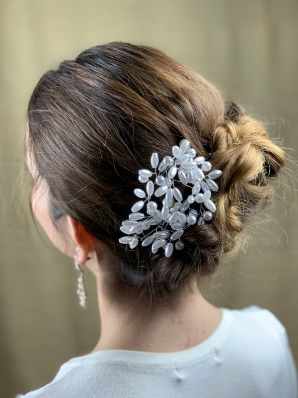 Back of brunettes head with decorated messy bun