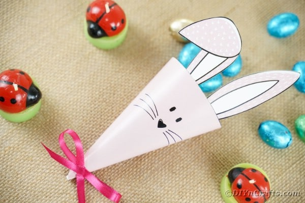 Paper Easter bunny cone candy holder on brown table