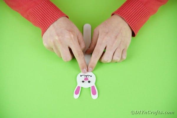 Gluing bunny head to craft stick