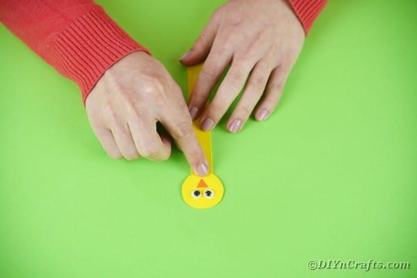 Gluing chicken head to craft stick