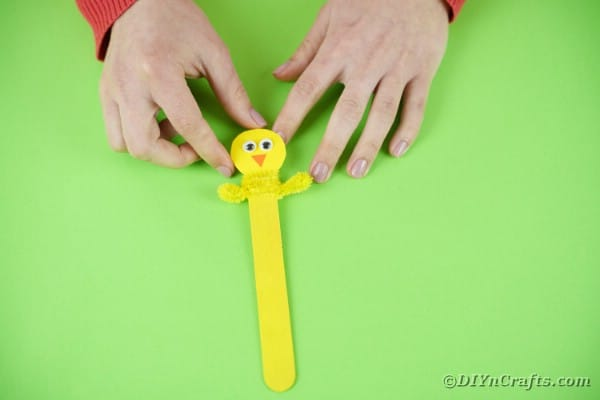 Adding pipe cleaner to craft stick for arms