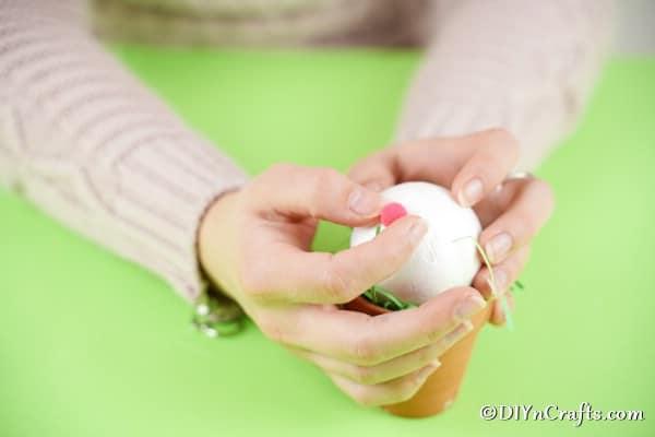 Gluing pom pom to styrofoam ball