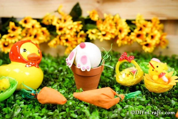 Easter bunny flower pot in front of yellow flowers