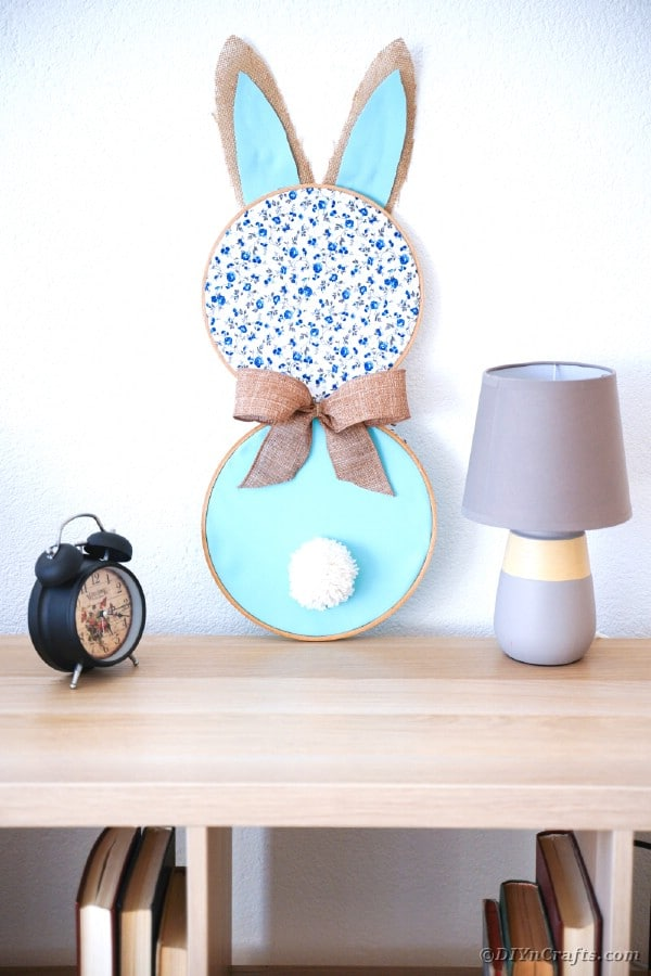 Fabric bunny wall art on table by lamp