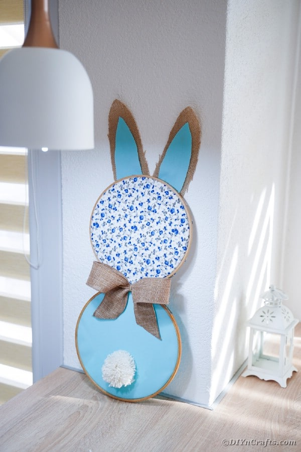 Bunny wall art leaning against wall on table