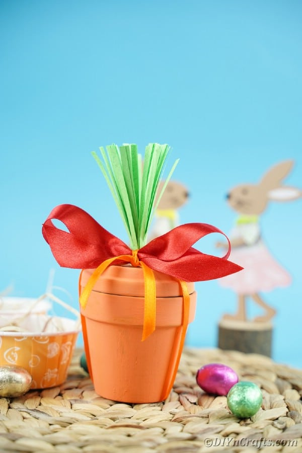 Flower pot carrot on woven mat in front of blue background