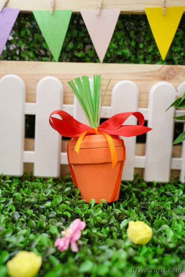 Flower pot carrot in front of white fence
