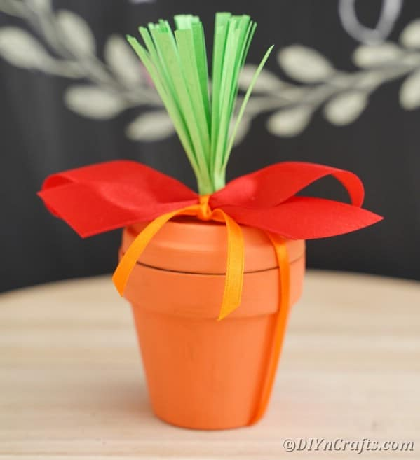 Flower pot carrot on table in front of chalkboard