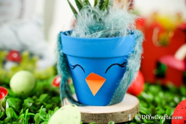 Blue flower pot bird sitting on a wood slice