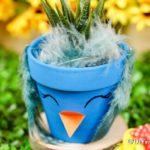 Blue flower pot bird on wood slice with grass