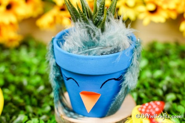 Blue flower pot bird on wood slice with grass