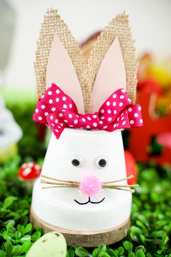 Flower pot bunny with pink bow on grass