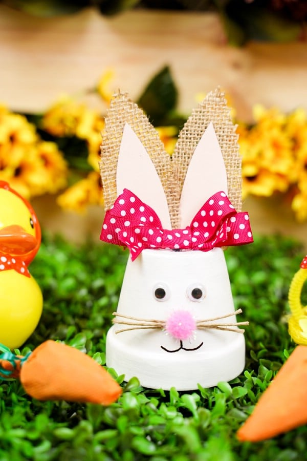 Upcycled flower pot Easter bunny on fake grass with yellow flowers