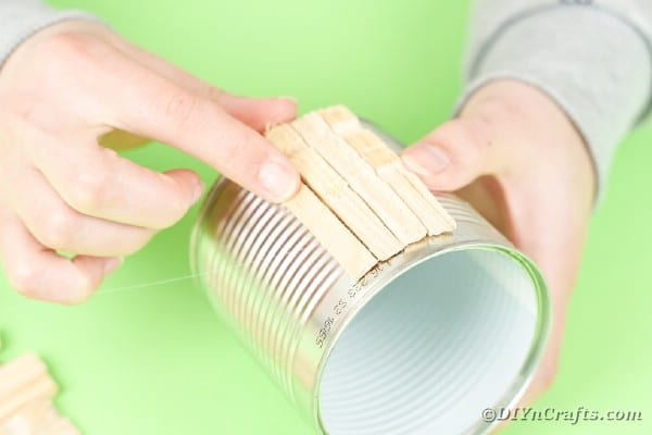 Gluing clothespins on tin can