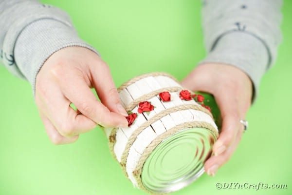 Gluing roses on tin can organizer