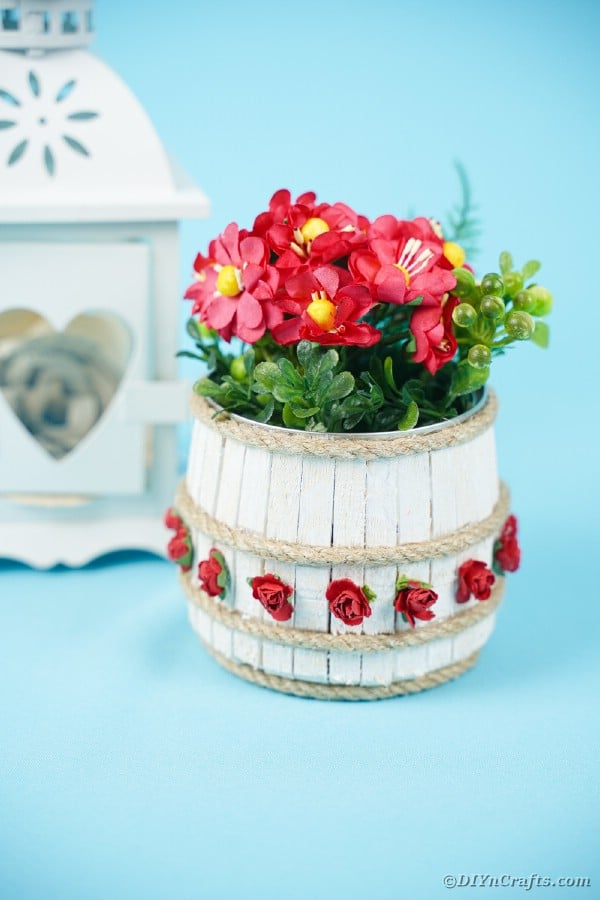 Mini wooden barrel on blue table with white lantern and red flowers