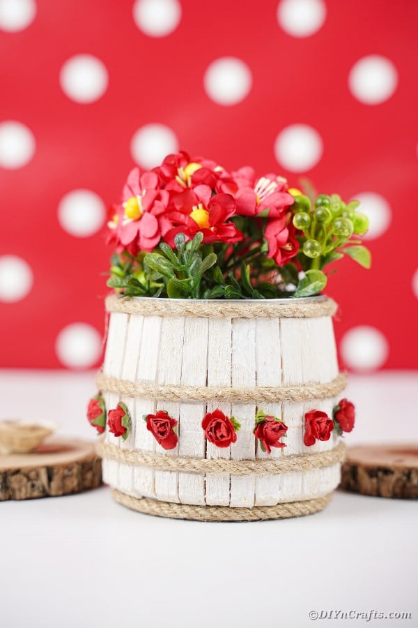 Clothespin barrel tin can in front of red polka dot background