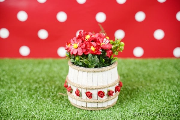 Clothespin tin can organizer on grass with red polka dot background