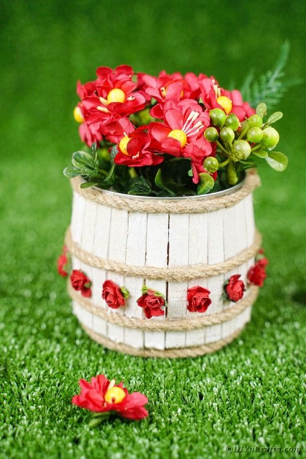 Mini wooden barrel planter on grass with flowers