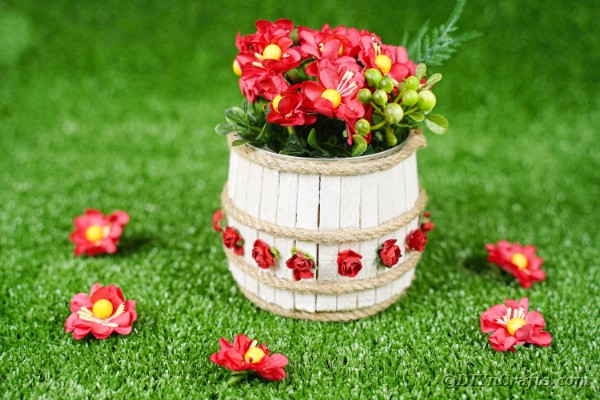 Tin can clothespin barrel on grass with red flowers