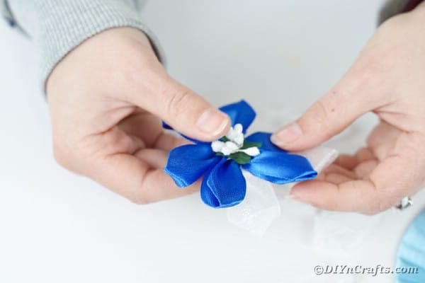 Gluing a flower into ribbon flower