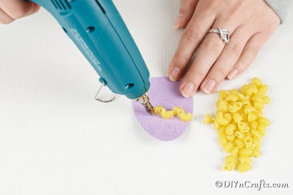 Gluing pasta in place on paper eggs