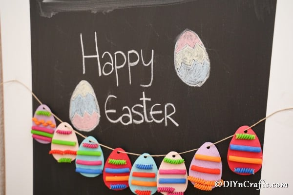 Painted pasta Easter egg garland hanging on chalkboard