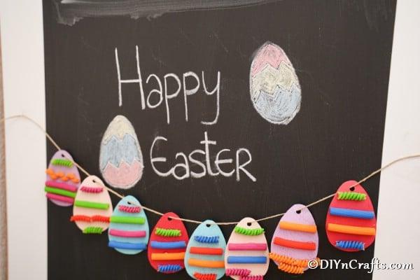 Painted pasta Easter egg garland hanging on chalkboard
