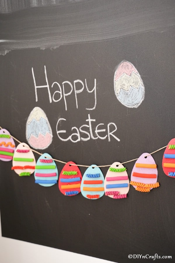 Easter egg garland hanging against chalkboard