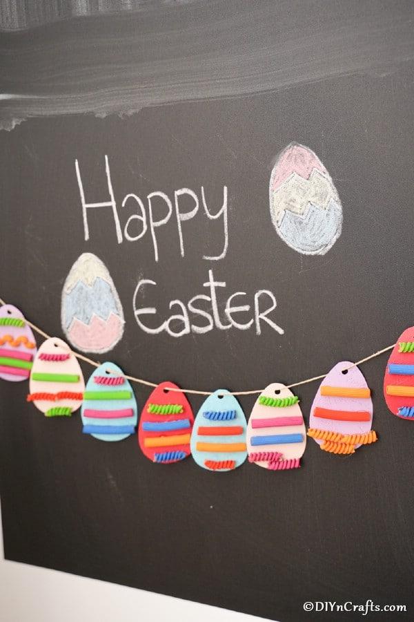Easter egg garland hanging against chalkboard