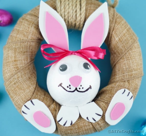 Rustic burlap easter bunny wreath hanging on blue wall