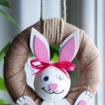 Easter bunny wreath hanging in front of plant