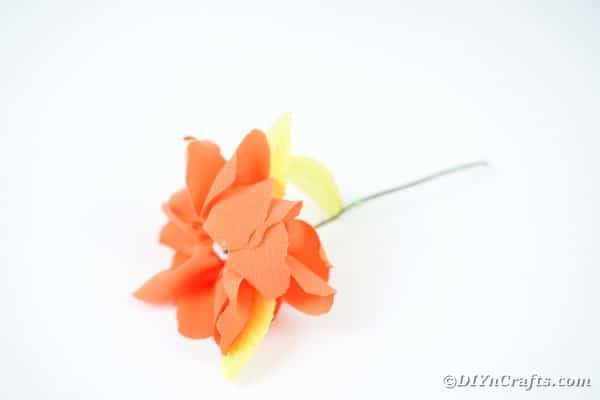 Orange fabric flower laying on white table