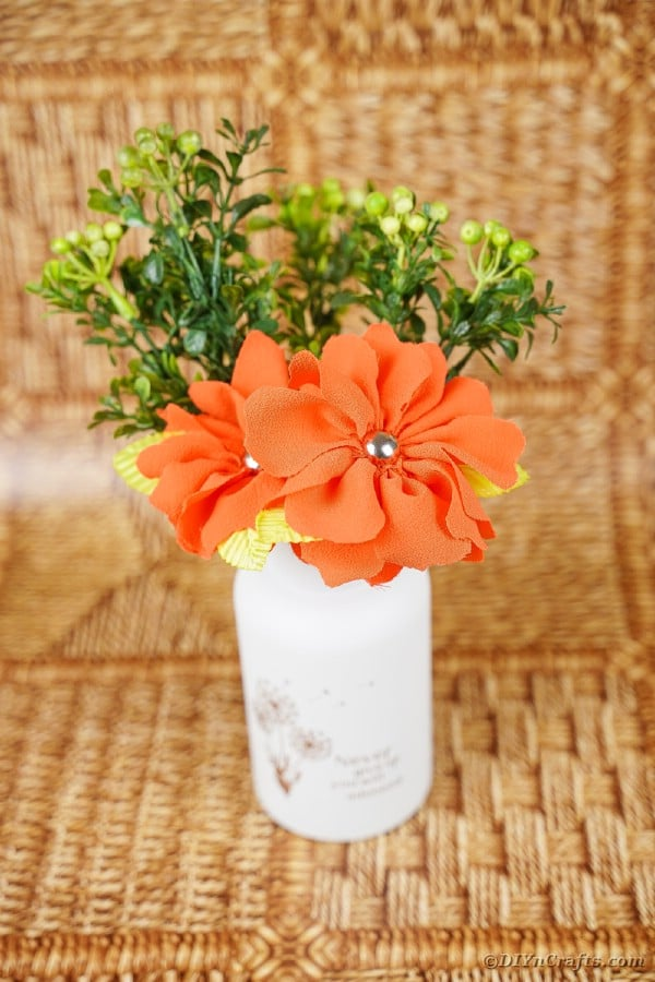 Jar of orange flowers with greenery on wood surface