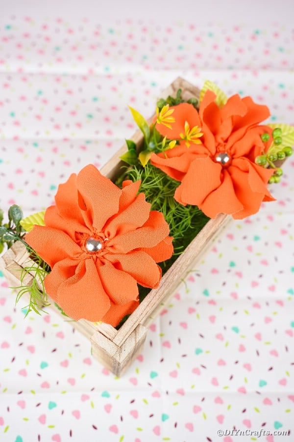 Wood box of orange flowers on patterned fabric surface