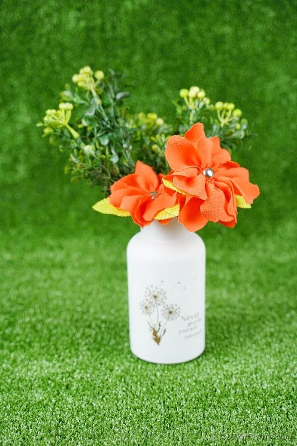 Orange flowers in white jar on grass