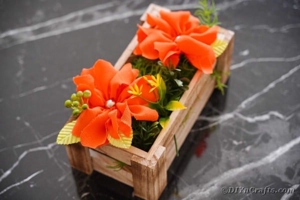 Orange flowers in wood box on marble table