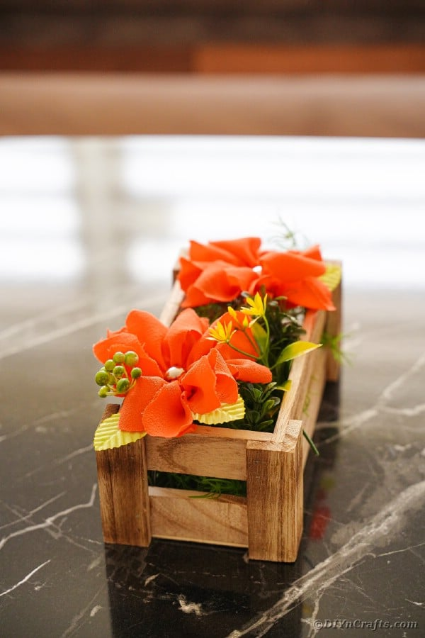 Orange fabric flowers in wooden box on table