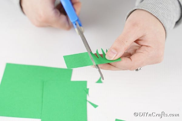Cutting green paper for grass
