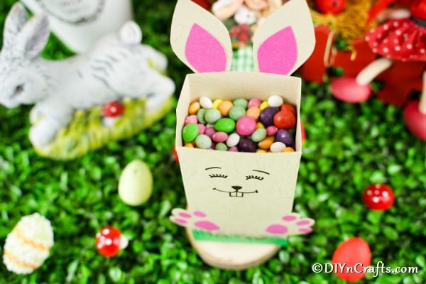Easter candy holder filled with candy on grass