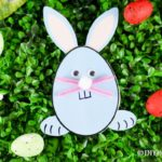 Easter bunny egg shaped card on grass with other eggs