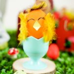 Blue egg cup with decorated chicken easter egg