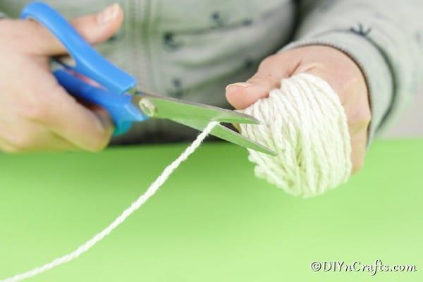 Cutting yarn off pom pom