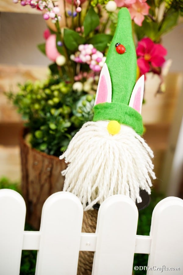 Easter gnome by white picket fence