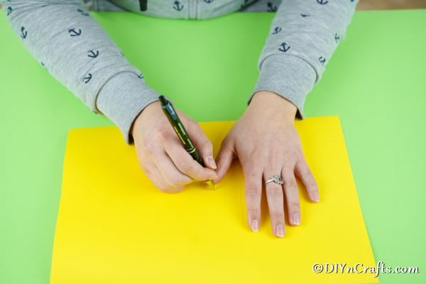 Tracing a hand on yellow paper
