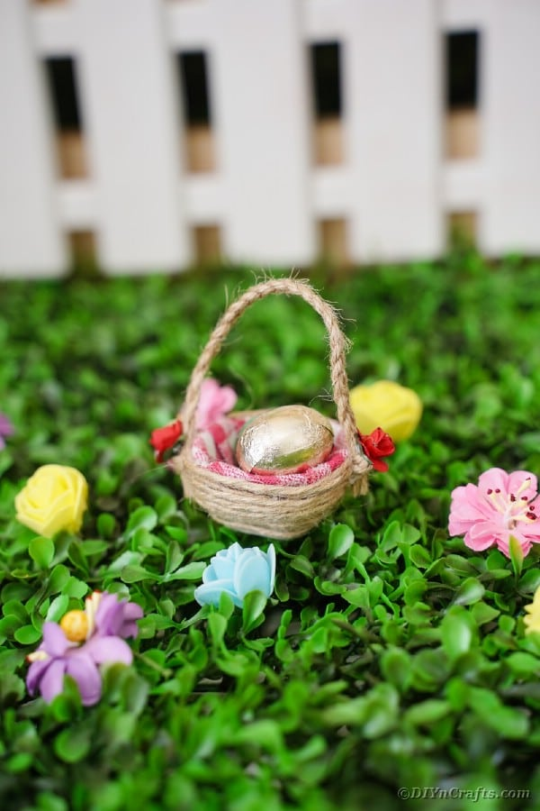 Egg carton Easter basket on grass in front of mini fence