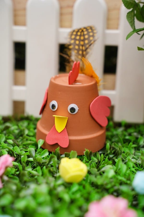 Flower pot chicken on grass in front of white fence