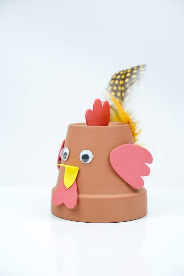 Terra cotta flower pot bird with yellow feathers
