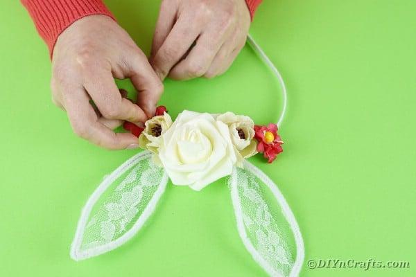 Adding flower to each ear on headband