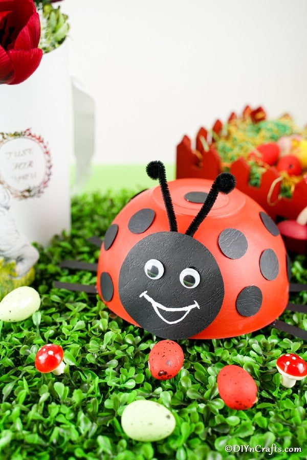 Upcycled bowll adybug on grass with other fake bugs
